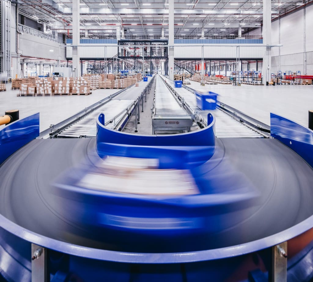 Conveyer belt with warehouse in background